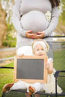 Pregnant mom behind cute baby girl sitting in chair holding blank blackboard