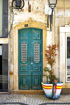 The turquoise wooden door on the promenade in Olhao, Algarve, Portugal, Europe