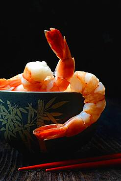 Cooked prawns in shell with chopsticks, Germany, Europe