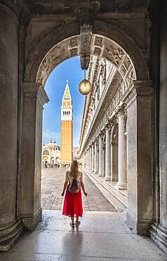 Young woman in portico at St. Mark's Square, with Campanile bell tower, Venice, Veneto, Italy, Europe