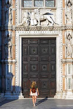 Young woman in front of the entrance to the Doge's Palace, St. Mark's Square, Venice, Veneto, Italy, Europe