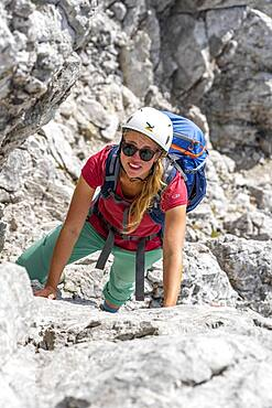 Young female hiker climbing with helmet, rocky mountains and scree, hiking to the Hochkalter, Berchtesgadener Alpen, Berchtesgadener Land, Upper Bavaria, Bavaria, Germany, Europe