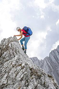 Young female hiker with helmet, rocky mountains and scree, hiking to the Hochkalter, Berchtesgadener Alpen, Berchtesgadener Land, Upper Bavaria, Bavaria, Germany, Europe