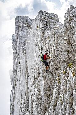 Young man climbing a vertical rock face without a rope, rocky mountains and scree, near Hochkalter, Berchtesgadener Alpen, Berchtesgadener Land, Upper Bavaria, Bavaria, Germany, Europe