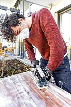 Young man doing DIY, grinding table with a grinder
