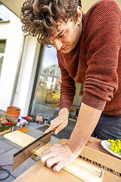 Young man doing DIY in his apartment, sawing board with a handsaw