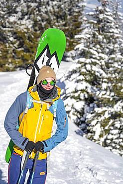 Young man with snowboard on his back, ski tourer on tour to Teufelstaettkopf, Ammergau Alps, Unterammergau, Bavaria, Germany, Europe