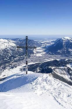 Alpspitz summit with summit cross, ski tour to the Alpspitze, view to Garmisch-Patenkirchen, Wetterstein mountains with snow in winter, Garmisch-Partenkirchen, Bavaria, Germany, Europe
