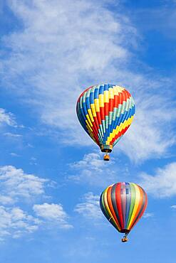 Beautiful hot air balloons against a deep blue sky and clouds