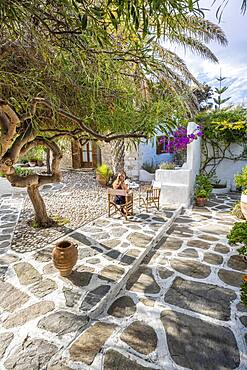 Courtyard, Greek home, Young woman having breakfast on holiday outside, Greece, Europe