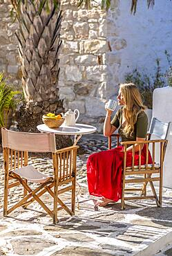 Young woman holding cup, breakfast on holiday outside, Greece, Europe