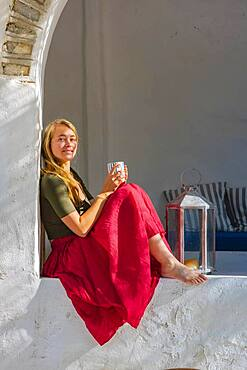 Young woman holding cup and sitting on wall, Greece, Europe
