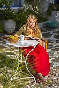 Young woman reading, breakfast on holiday, courtyard, Greece, Europe