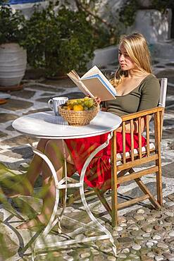 Young woman reading a book, breakfast on holiday, courtyard, Greece, Europe