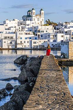 Young woman with red dress on harbour wall, behind church of Naoussa, harbour town Naoussa, island Paros, Cyclades, Greece, Europe