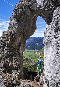 Hiker standing in the rock gate Breitensteinfensterl with view of high fog over the valley, hiking trail to Breitenstein, Fischbachau, Bavaria, Germany, Europe