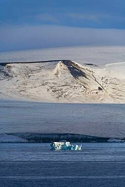 Iceberg floating before the flat table mountains covered with ice, Franz Josef Land archipelago, Russia, Europe