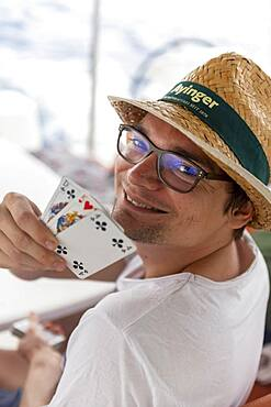 Young man grins and shows playing cards, deck of cards, board games