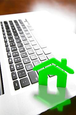House icon resting on laptop keyboard