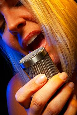 Female vocalist under gelled lighting sings with passion into condenser microphone