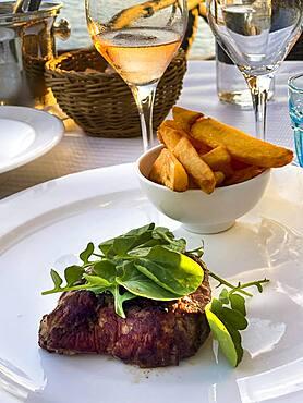 Grilled fillet steak in the evening sun by the sea, Port de Andratx, Majorca, Spain, Europe