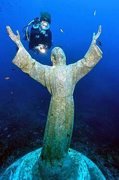 Diver looking at statue of Christ, Mediterranean Sea, San Fruttuoso, Portofino Peninsula, Liguria, Italy, Europe
