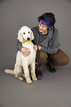 Woman with white king poodle, studio shot, Germany, Europe