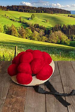 Black Forest Bollen hat on wooden table in front of hilly landscape, Black Forest, Baden-Wuerttemberg, Composing, Germany, Europe