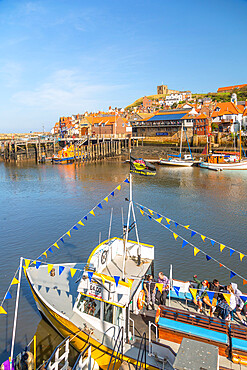 View of St. Mary's Church and restaurants, houses and boats on the River Esk, Whitby, Yorkshire, England, United Kingdom, Europe