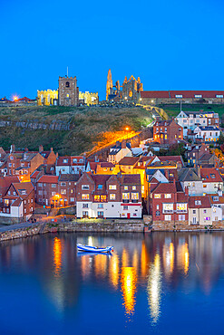 View of St. Mary's Church and Whitby Abbey from across River Esk at dusk, Whitby, Yorkshire, England, United Kingdom, Europe