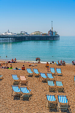 View of Brighton Palace Pier and blue and white striped deck chairs on the beach, Brighton, East Sussex, England, United Kingdom, Europe