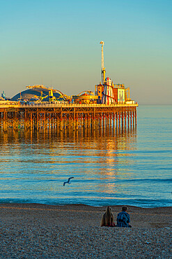 View of couple on beach and Brighton Palace Pier at sunset, Brighton, East Sussex, England, United Kingdom, Europe