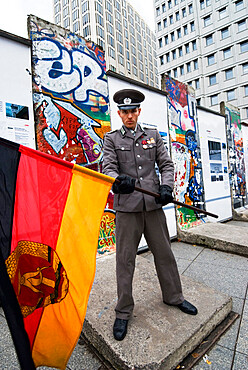 East German guard with former GDR flag in front of remains of the Berlin Wall, Potsdamer Platz, Berlin, Germany, Europe