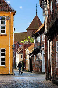 Cobblestone alley in the old town with tower of St. Catharinae Kirke, Ribe, Jutland, Denmark, Scandinavia, Europe