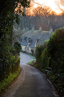 View down lane to Arlington Row Cotswold stone cottages at dawn, Bibury, Cotswolds, Gloucestershire, England, United Kingdom