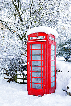Traditional British red telephone box covered in winter snow, Snowshill, Cotswolds, Gloucestershire, England, United Kingdom, Europe