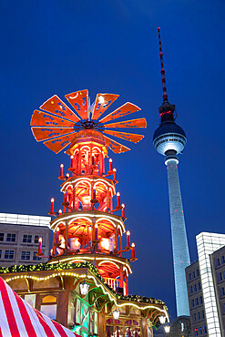 Christmas Pyramid at Christmas market in Alexanderplatz with Fernsehturm television tower behind, Berlin-Mitte, Berlin, Germany, Europe