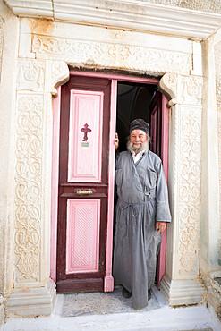 Greek Orthodox priest standing in doorway of Moni Taxiarchon Monastery, Serifos, Cyclades, Aegean Sea, Greek Islands, Greece, Europe