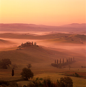 Tuscan farmhouse with cypress trees in misty landscape at sunrise, San Quirico d'Orcia, Siena Province, Tuscany, Italy, Europe