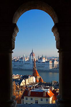 Parliament (Orszaghaz) and River Danube through arches of Fishermen's Bastion (Halaszbastya), UNESCO World Heritage Site, Buda, Budapest, Hungary, Europe