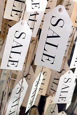 Sale tags in shop window, United Kingdom, Europe