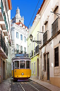 Tram (electricos) along Rua das Escolas Gerais with tower of Sao Vicente de Fora, Lisbon, Portugal, Europe