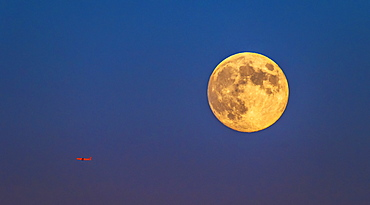 Plane flying across clear sky with full moon