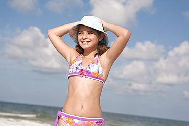 Portrait of girl on beach with hands behind head