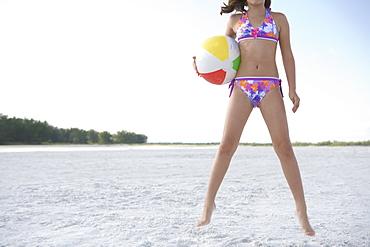 Girl in bikini jumping with beach ball