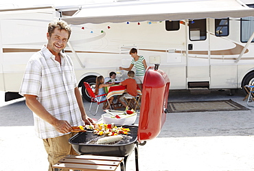 Man barbecuing with family and motor home in background