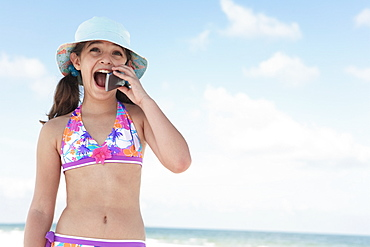 Girl on beach talking on cell phone