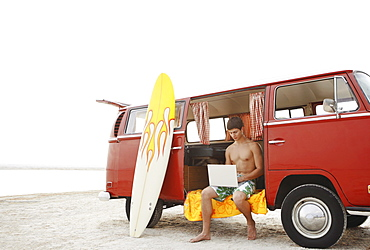 Young surfer using laptop in van on beach