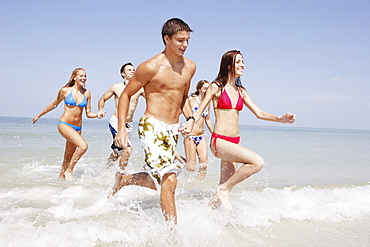 Friends running in ocean