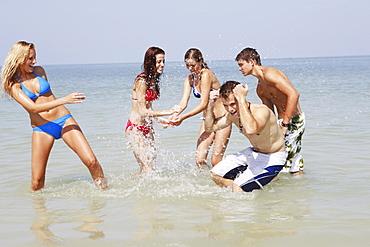 Friends splashing each other in ocean